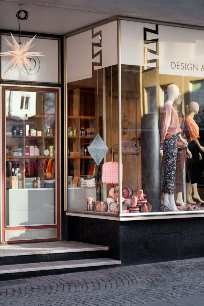 Blick auf den Eingang von Design + Handwerk Dickerhoff. Vor der Eingangstür ist ein Herrnhuter Stern, im Schaufenster sind viele Maileg Kuscheltiere platziert sowie Schaufensterpuppen mit nachhaltiger Damenmode.