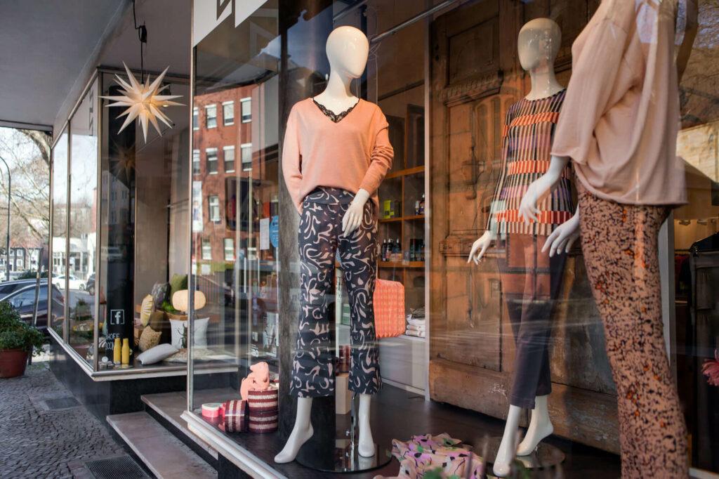 Schaufenster mit drei Figuren in modischer Kleidung, daneben sind verschiedene Produkte dekoriert, u.a. Herrnhuter Sterne