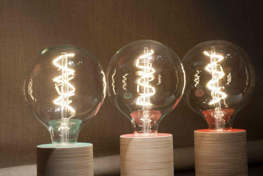 Moodbild von drei verschiedenen Design der Tischleuchten von Lichtliebe mit hölzernem Sockel und einer großen Glühbirne als Leuchtmittel.