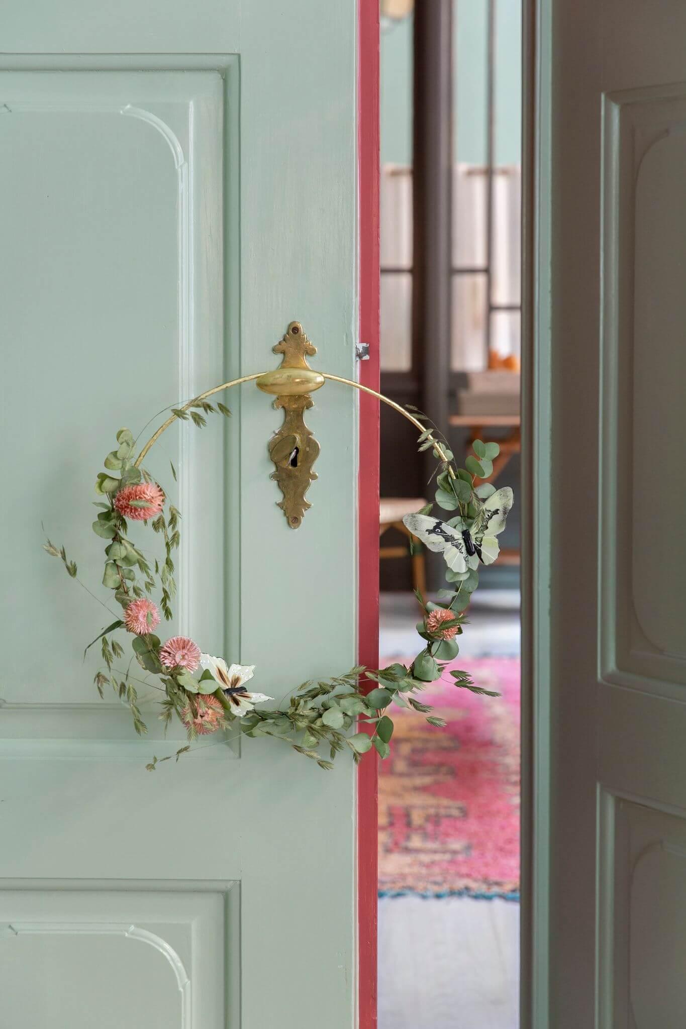 Moodbild eines goldenen Dekorationsrings umwickelt mit verschiedenen Blüten und Zweigen vor einer mintfarbenen Holztür.