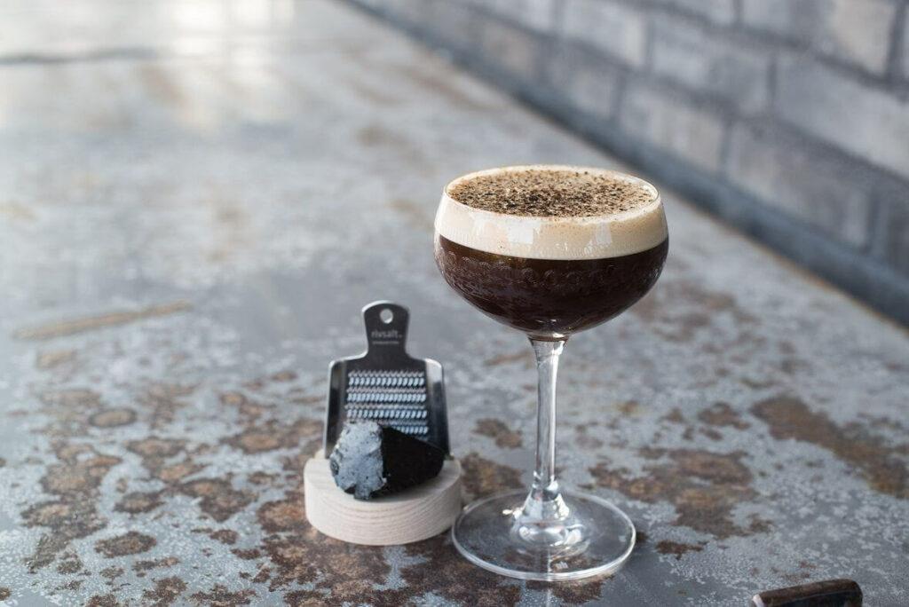 Moodbild eines Espresso-Cocktails neben einer Lakritzreibe mit frischem Lakritz.