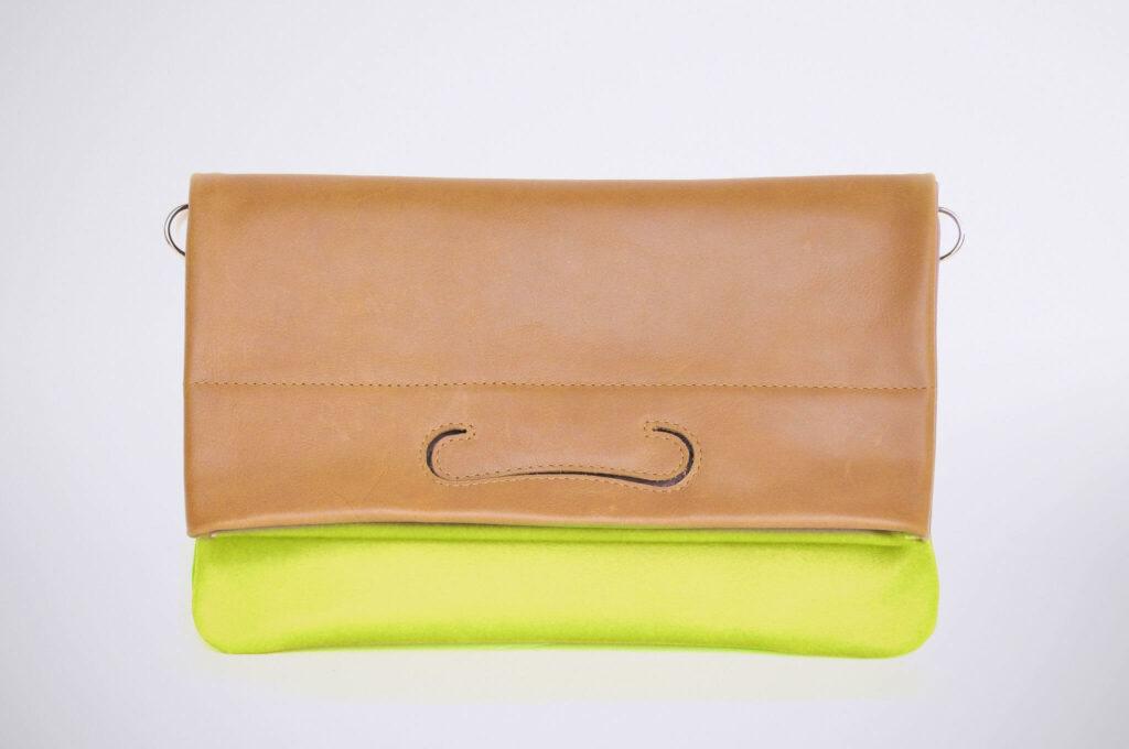Freisteller einer handgemachten Lederclutch in neon-gelb und cognacfarbenem Leder als Überschlag.