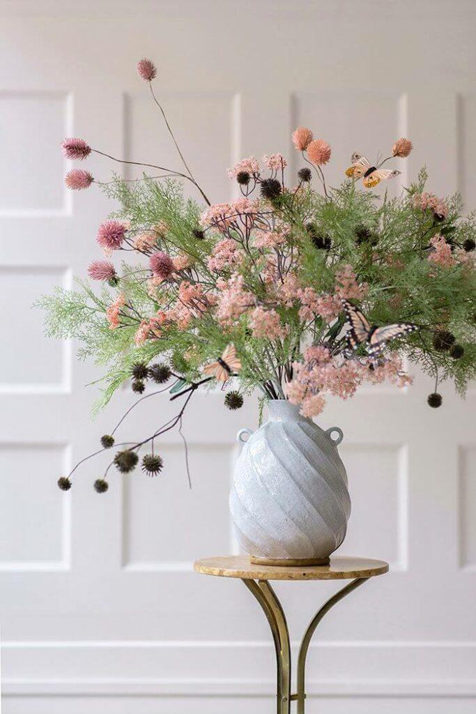 Moodbild verschiedener Kunstzweige von Bungalow Denmark in einer grauen Vase auf einem kleinen Beistelltisch vor einer weißen Holzwand.