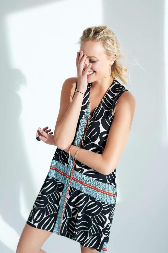 Model mit kurzem Kleid in A-Linie mit grafischem Muster in schwarz und weiß, abgesetzt mit einem hellblau/weißen Stoff und roten Details.