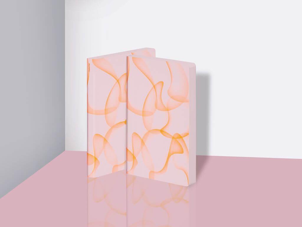 Freisteller eines Nuuna Notizbuchs in rosa mit neon orange-farbenen organischen Formen bedruckt.