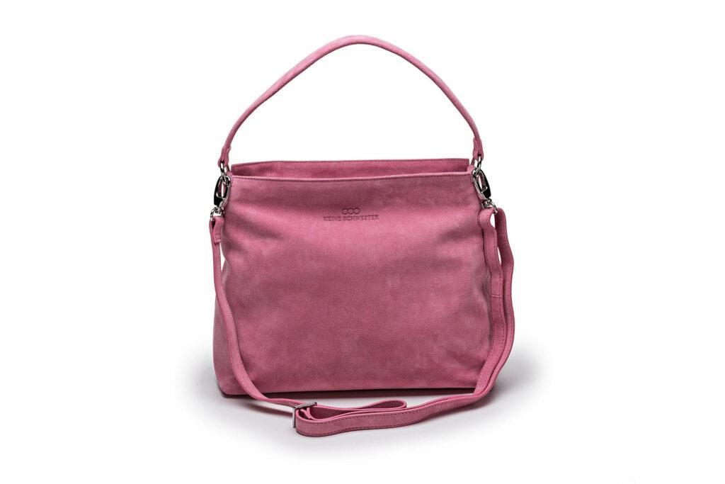 Freisteller einer Wildledertasche von keine Schwester in Trapezform mit Umhängegurt in rosa.
