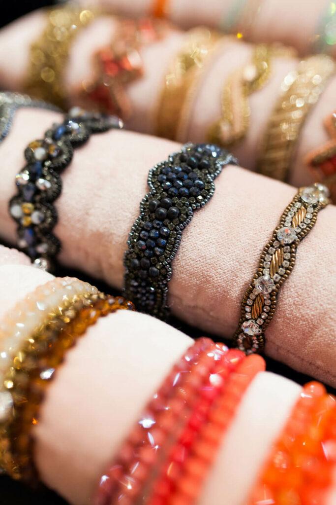 Moodbild verschiedener Armbänder aus Glas-, Keramik-, Stoffperlen und verschiedener anderer Materialien auf rosafarbenen Samtkissen.