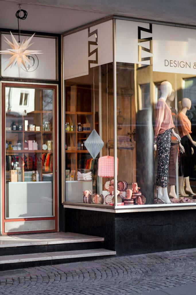 Schaufenster des Ladengeschäfts Design + Handwerk Dickerhoff mit Fokus auf eine Herrnhuter Stern-Lampe über dem Eingang, Dekoartikeln und Schaufensterpuppen mit farbenfroher Mode.
