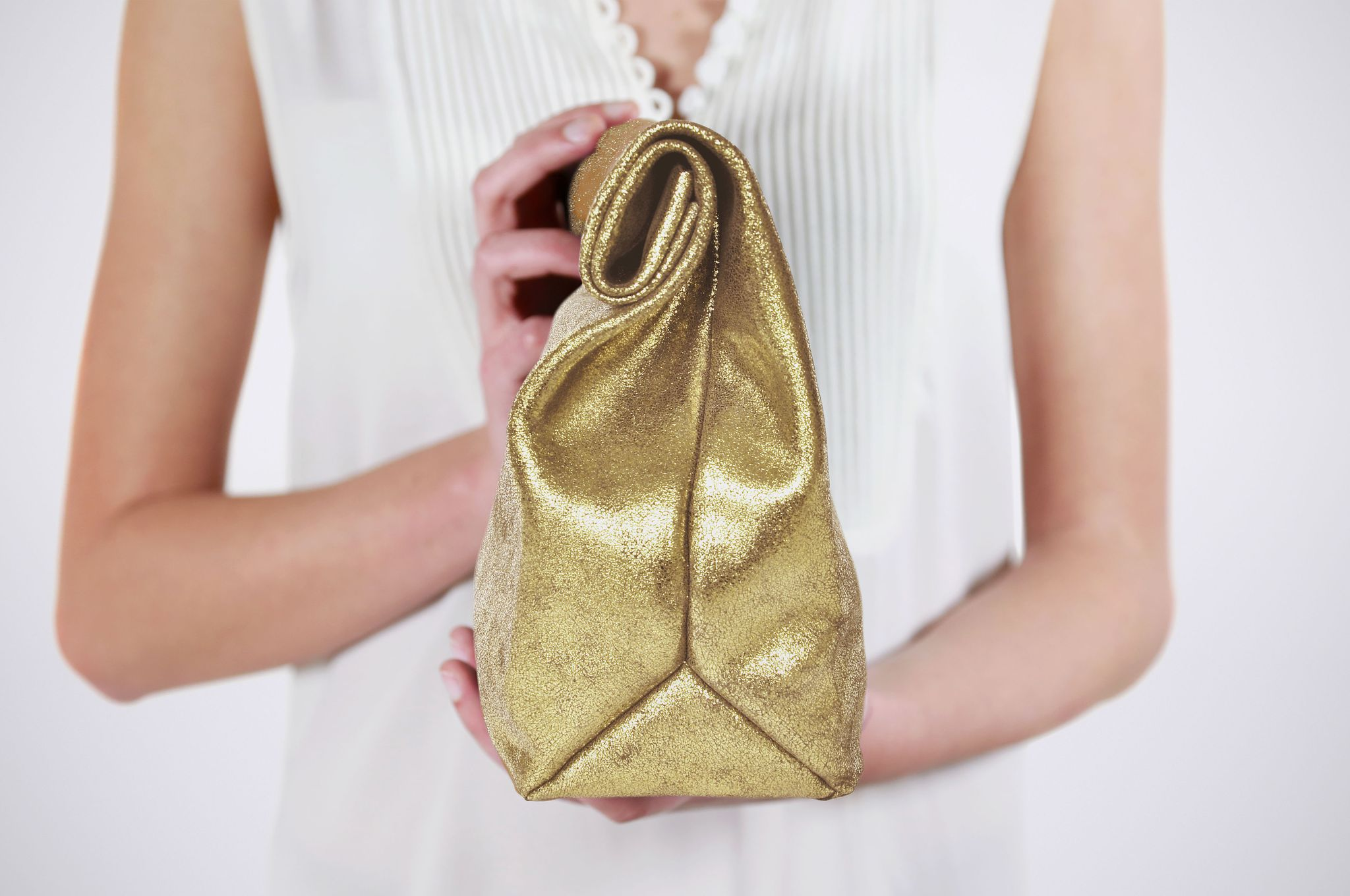 """Model mit goldener Handtasche aus Nubukleder im Paper Clutch-Stil, die oben """"zusammengerollt"""" wird."""