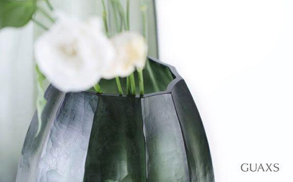 Moodbild einer Guaxs Vase aus grünem Glas mit geometrischem Schliff.