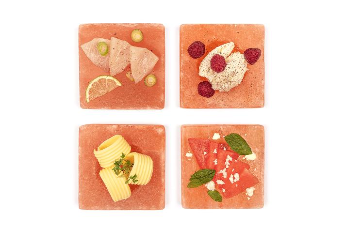 Auf vier verschieden Rivsalt Freeze and Serve Platten aus rosa Salzstein sind verschiedenste Speisen angerichtet, u.a. Butter, Fisch und Obst.