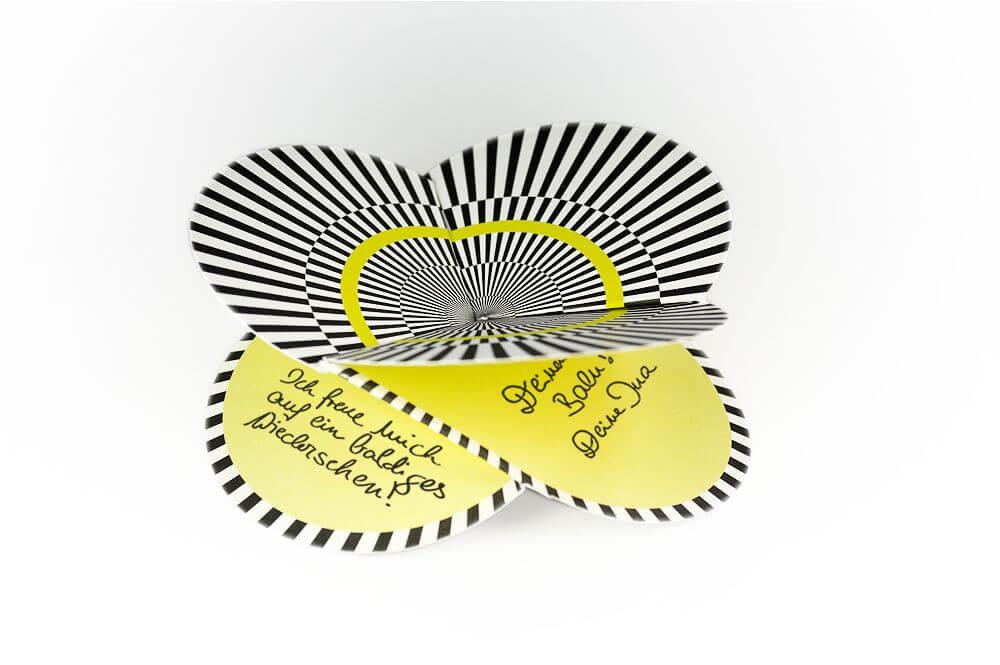 Faltkarte mit geometrischem Muster in schwarz, weiß und gelb.
