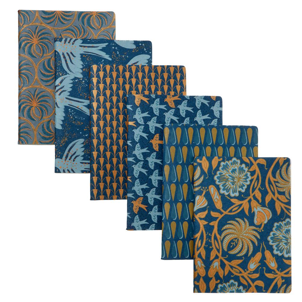 Freisteller von Papeterie-Artikeln, insbesondere Notizbüchern, in blau- und gold-Tönen mit geometrischen Mustern bzw. Naturmotiven.