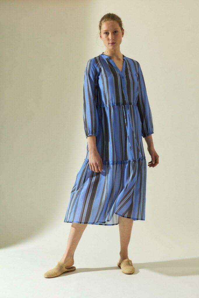 Model in Midi-Kleid in mittelblau mit Volants und Längsstreifen in hellblau und braun.