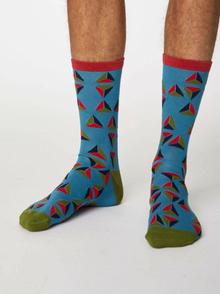 Model mit blauen Socken mit geometrischem Motiv in blau, rot und grün, an der Hacke und Spitze grün, am Bündchen rot.