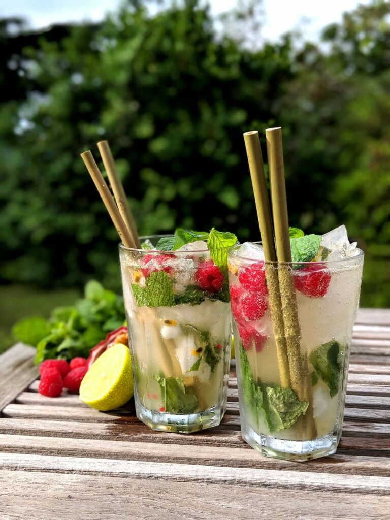 Moodbild von zwei fruchtigen Cocktails auf einem Holztisch, in denen jeweils zwei Bambus-Strohhalme stecken.