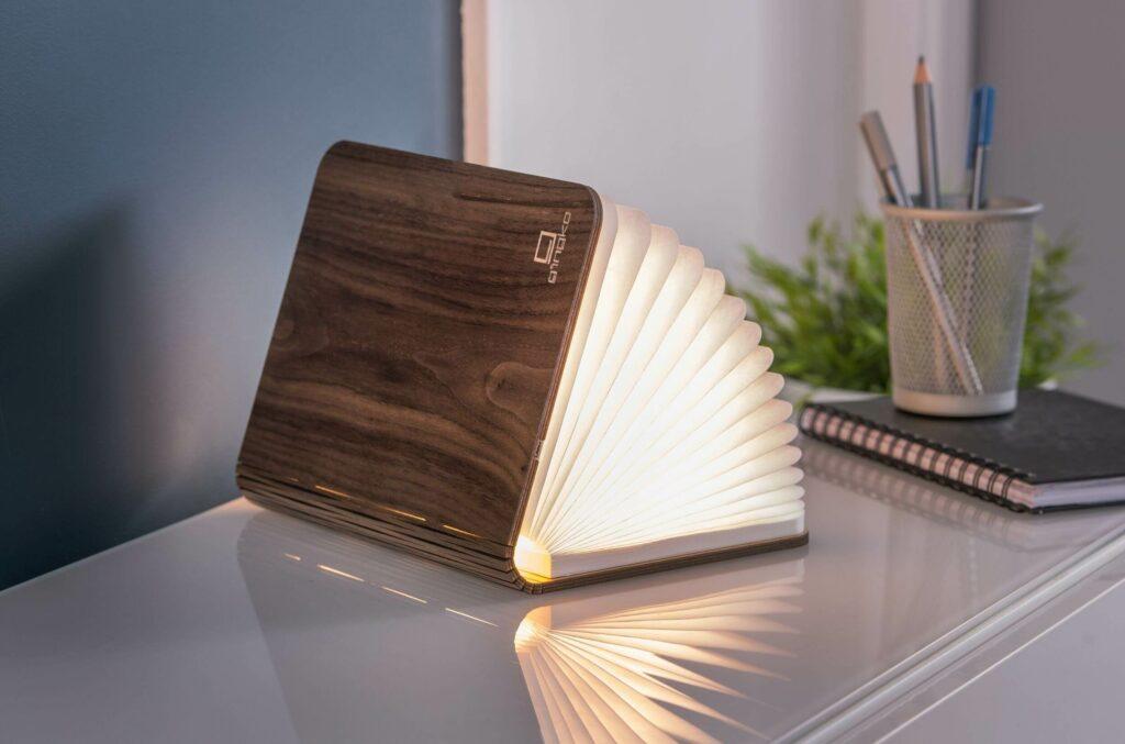 """Moodbild einer Lampe in Buchform, die man flexibel weit öffnen kann, je nach Lichtbedarf. Hinter den durchscheinenden, zusammenhängenden """"Seiten"""", ist eine Lichtquelle."""