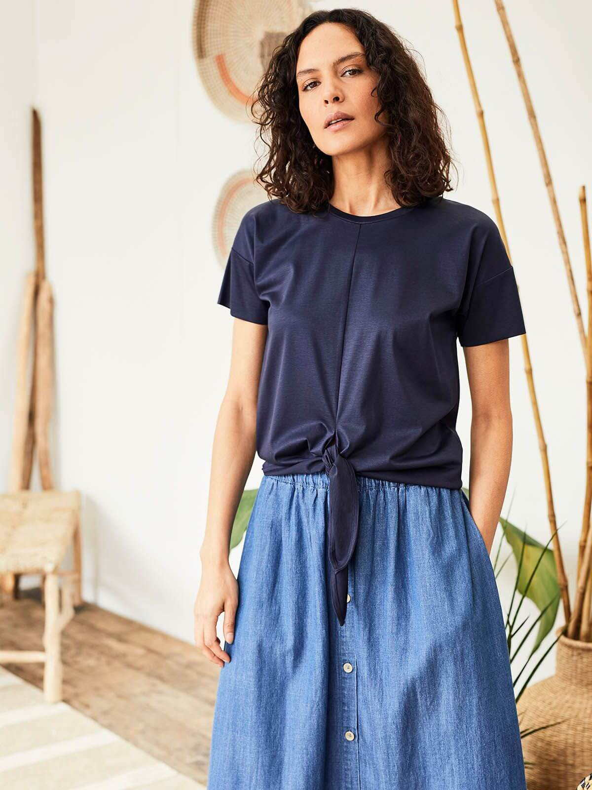 Moodbild Model mit dunkelblauem Shirt, vorne geknotet, und Jeans-Rock vor hölzerner Dekoration.
