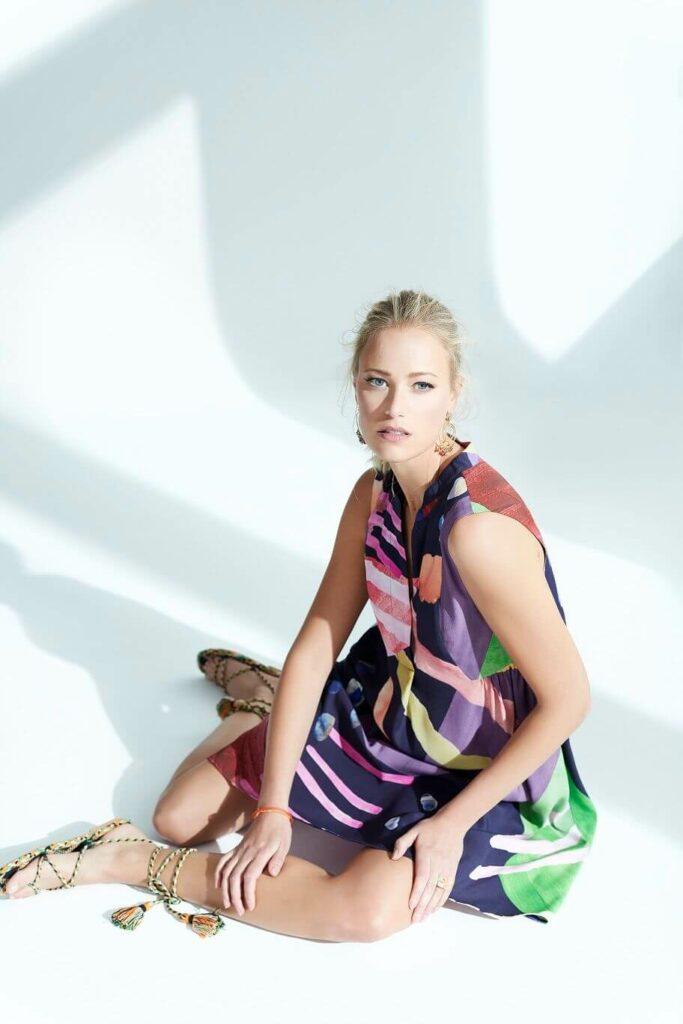 Model in buntem Hemdkleid mit geometrischem Muster in lila, gelb, grün und rot.