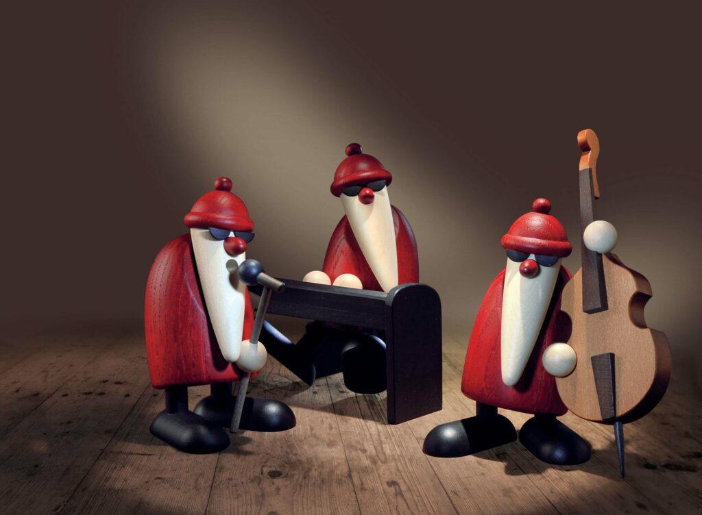 Moodbild Weihnachtsmann-Band von Björn Köhler (Piano, Gesang und Kontrabass), platziert vor einer braunen Wand auf Holzboden.