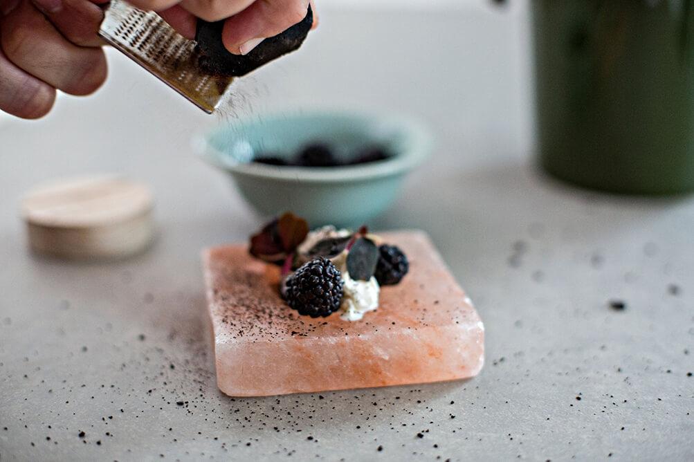 Auf einer Rivsalt Freeze and Serve Platte aus rosa Salzstein sind Brombeeren und eine Creme platziert, darüber wird rohes Lakritz an einer Reibe gehobelt.