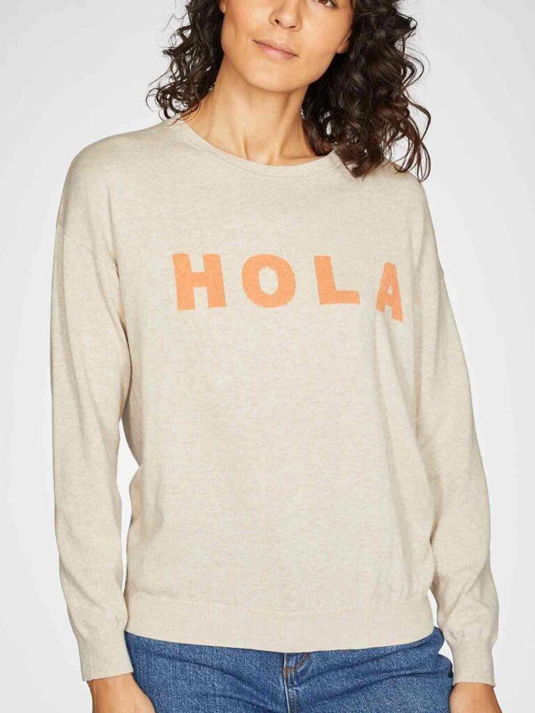 Model in hellbeigem Pullover mit korallfarbenem Hola Schriftzug und blauer Jeans.