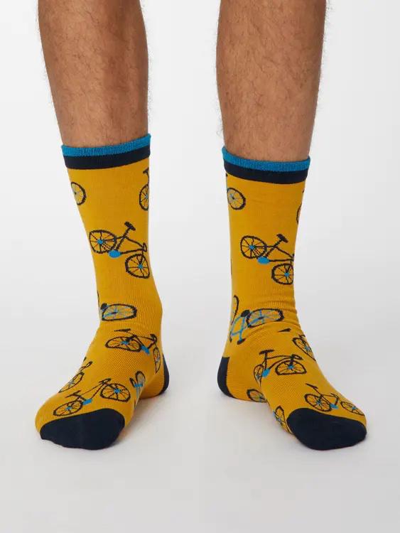 Model mit gelben Socken mit Fahrradmotiv, an der Hacke und Spitze dunkelblau, am Bündchen hell- und dunkelblau geringelt.