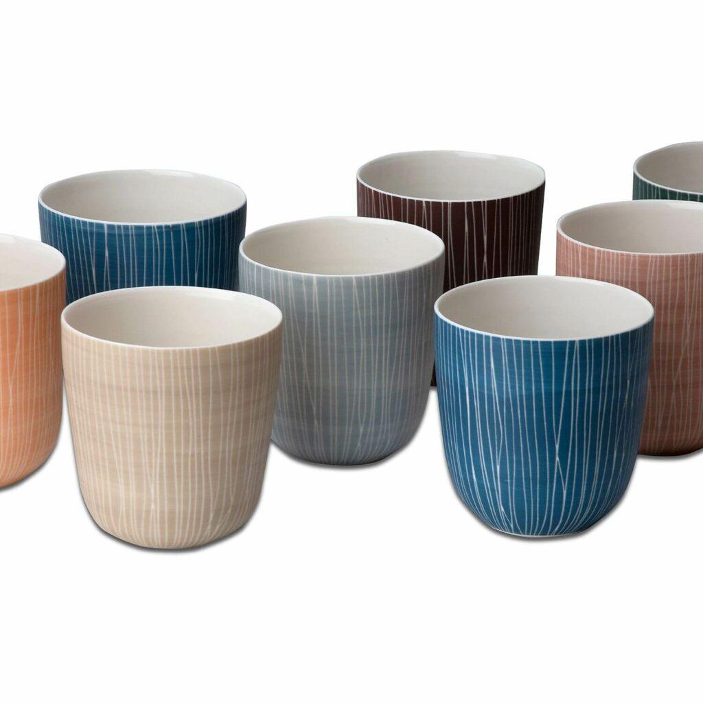 Verschiedene Tassen/Trinkbecher handgemacht von Anna Sykora ohne Henkel, japanisch anmutend, mit geometrischen Linien in braun-, blau- und rosé-Pastell-Tönen (Freisteller).