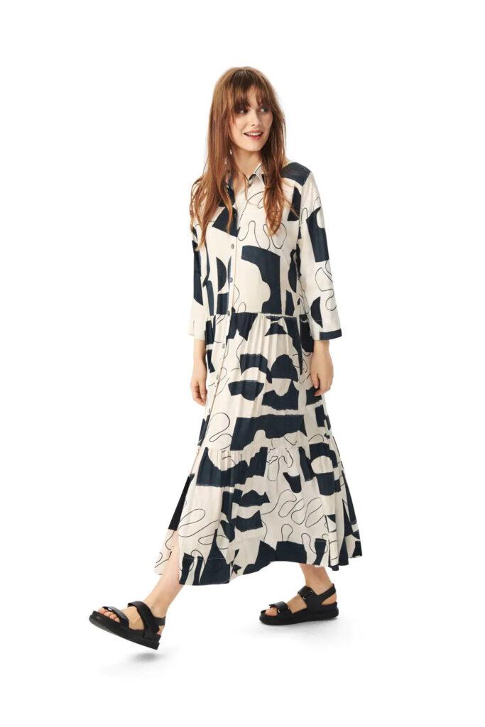 Model vor weißem Hintergrund trägt langes schwarz-weißes Kleid mit Monsteraprint im One-Line-Design.
