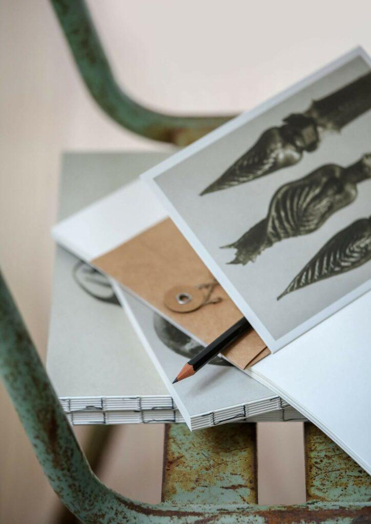 Moodbild einer Sköna Ting Grußkarte und weiterer Papeterieprodukte auf einem grünen Metallstuhl.
