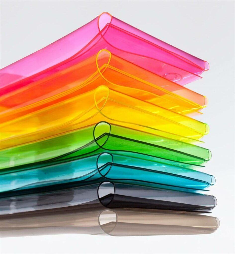 Sieben verschieden farbige, fluoreszierenden Taschen aus halbtransparentem Vinyl in Briefform sind aufeinander gestapelt.