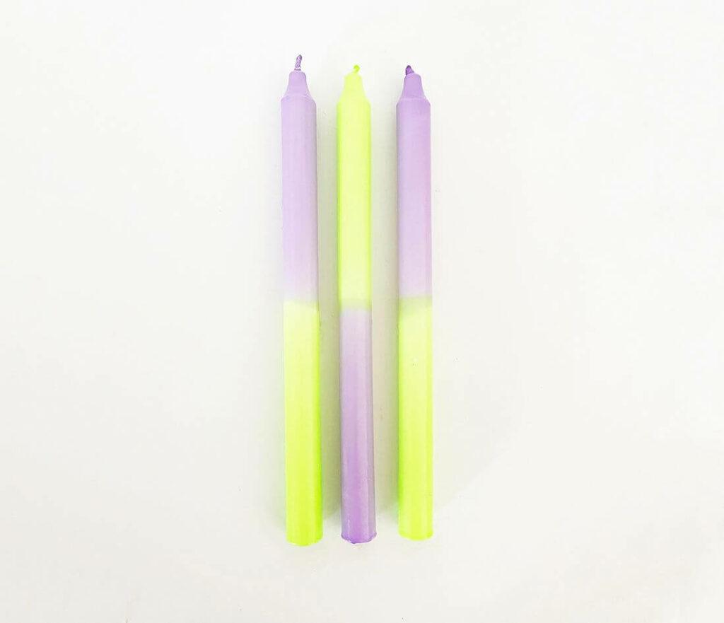 Freisteller von drei Dip Dye Kerzen in neongelb und -lila.