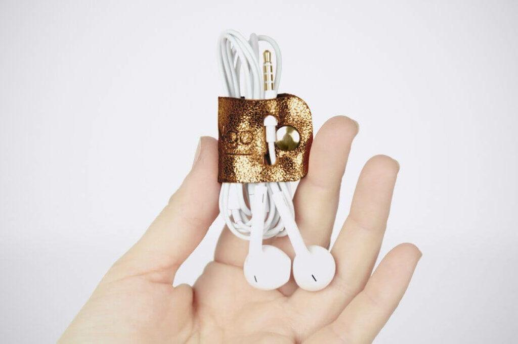 Model mit Kabelorganizer aus bronzefarbenem Leder zur sicheren Aufbewahrung von Kopfhörern.