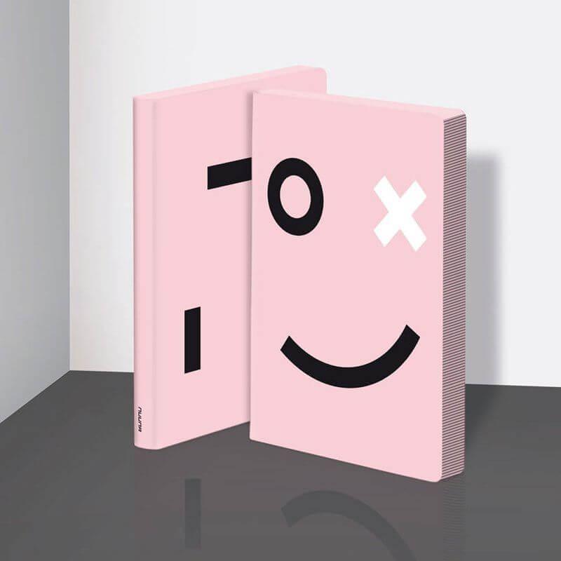 Freisteller eines Nuuna Notizbuchs in pink mit Smiley aus geometrischen Formen (schwarz & weiß) auf der Vorder- und Rückseite.