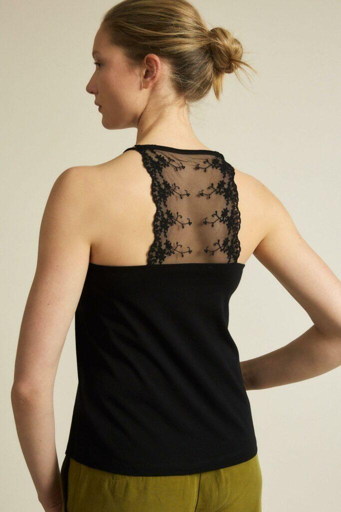 Model mit schwarzem Baumwolltop mit Spitze am Dekolleté abgesetzt sowie am oberen Rücken.